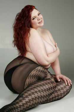 Curvy redhead is a topless tease