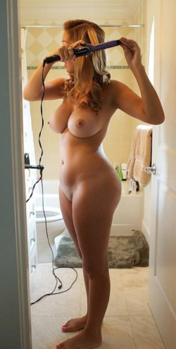 Curvy blonde doing her hair in the nude