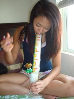 Cute Asian stoner girl demonstrates a bong rip