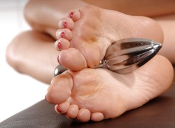 Foot Mistress Holds Butt Plug for Slave's Ass