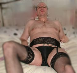 Adrian posing in his stockings and suspenders