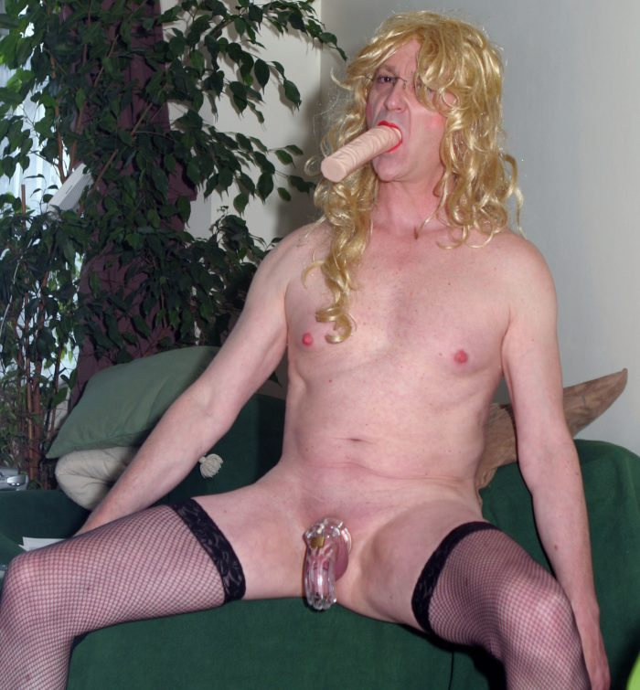 sissy drew gets the dildo nice and wet, legs spread wide, nice view of that skinned back caged c ...